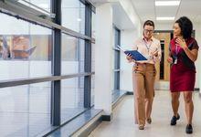 Two teachers talking and walking down a school hallway