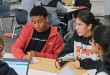 A diverse group of four high school students collaborate at a table at Dayton STEM school
