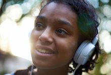 Black teen with headphones on while outside