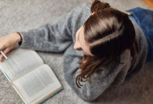 Teenage girl reading book on floor at home.
