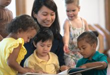 Teacher reading a book to a small group of preschool students