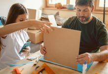 Father and daughter making 3D cardboard models at home