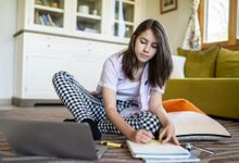 Teenage girl sitting on floor of room doing homework with laptop and books.
