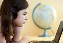 Pre-teen girl looks at laptop screen with a globe in background.