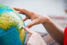 Hand pointing to African continent on globe.