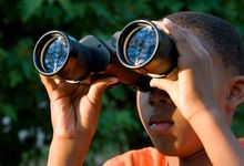 Boy looking through binoculars outside.