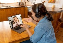 Primary teacher and pupil interacting in live video lesson. Woman tutor with headset and laptop working remotely from home online teaching child student in video conference.