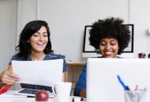 Two women collaborating with a laptop