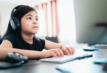 Young girl at home on computer doing distance learning.