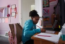 Middle school-aged girl working at home during distance learning