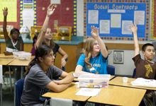 Middle school students in social studies class raise their hands