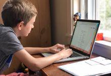 Boy doing homework on his laptop