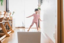 Pre-kindergarten aged girl dancing in front of laptop at home.