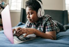 Boy using his laptop in his room with headphones on