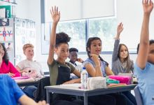 Students raise hands in middle school classroom