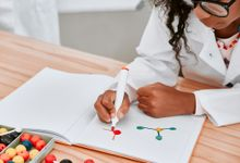 Girl in lab coat drawing an atom from a science experiment