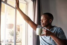 Man in the morning, looking out window holding coffee