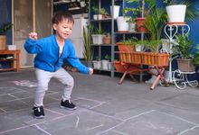 Preschool-aged boy playing hopscotch at home