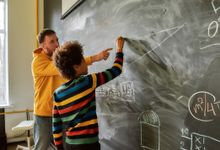 Teacher with student doing math on chalkboard