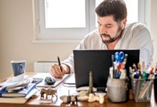 Man takes notes while working on his laptop