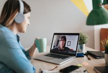 Woman drinking coffee during a video meeting at her desk at home