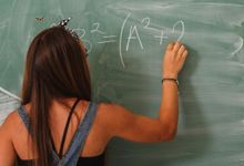 Teenage girl doing math problems on chalkboard
