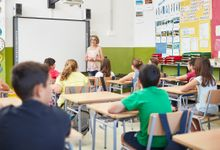 Teacher speaking to students in middle grade classroom