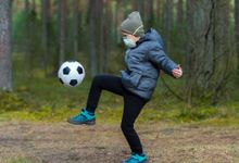 Boy kicking a soccer ball outside while wearing a mask