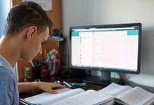 Teenage boy doing homework in front of computer