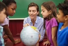 Teacher with elementary students looking at globe