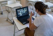 Teacher leading a virtual lesson in her empty classroom