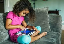 Young girl using an ipad on her couch at home