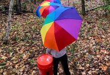 Elementary aged girl walks to her outdoor classroom carrying an umbrella and 5-gallon bucket