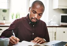 Man at home writing in notebook