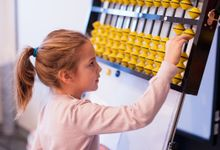Elementary aged girl uses abacus at school