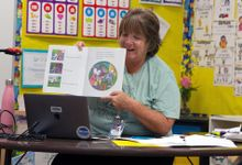 A second grade teachers reads to her students during virtual story time