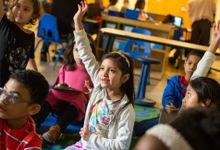 A third grader raises her hand in class