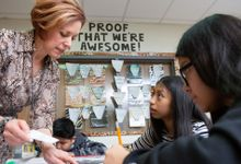 Science teacher works with two students