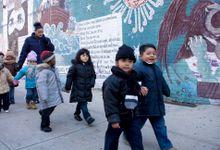 Preschool students walking in pairs on a sidewalk with their teachers