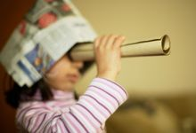 Young girl playing make believe with a newspaper hat and looking through paper roll.