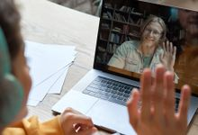 Teenager participating in a virtual meeting with her teacher on her laptop