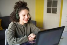 Teenage girl smiling during remote learning class on laptop at home