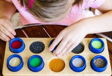 Child with poor vision is touching the wooden tactile rolls of different texture and colour as a part of educational therapy.