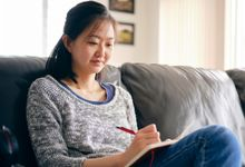 Adult woman writing in journal at home on couch