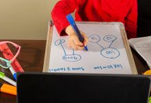 Student writing on a small whiteboard during a distance learning assignment