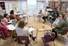 Group of teachers meet in a classroom