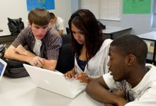 Three high school students work on a laptop together
