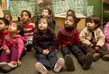 Pre-school students sitting on floor in classroom