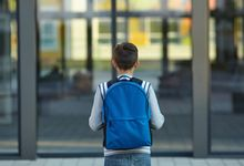 Schoolboy stands in front of the school door.