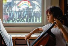 Pre-teen boy practicing cello at home with rainbow painted on window